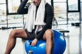 """Постер, картина, фотообои """"обрезанное изображение спортсмена, сидя на фитнес мяч с полотенцем и смартфон в тренажерный зал"""""""