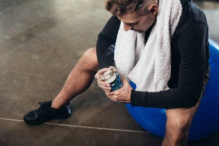 Photo for High angle view of handsome tired sportsman sitting on fitness ball with towel and sport bottle in gym - Royalty Free Image