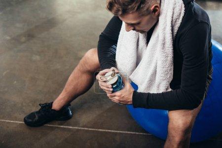 Photo pour Vue grand angle du beau sportif fatigué assis sur la balle de fitness avec serviette et bouteille de sport dans la salle de gym - image libre de droit