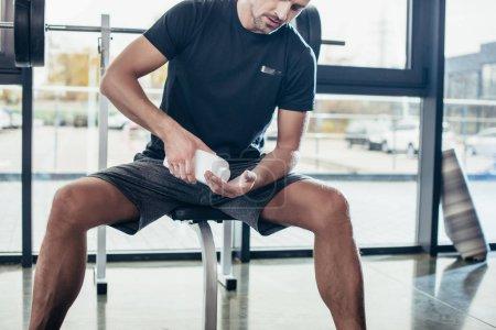 Photo pour Image recadrée de l'homme athlétique appliquant de la poudre de talc sur les mains avant l'entraînement dans la salle de gym - image libre de droit
