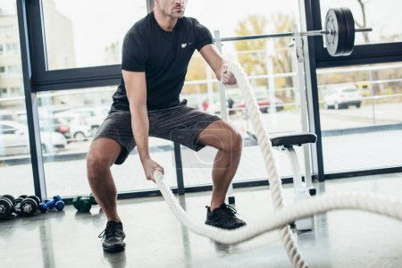 Photo for Cropped image of sportsman working out with ropes in gym - Royalty Free Image