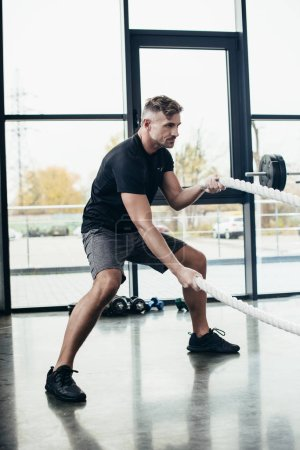 Photo for Side view of handsome sportsman working out with ropes in gym - Royalty Free Image