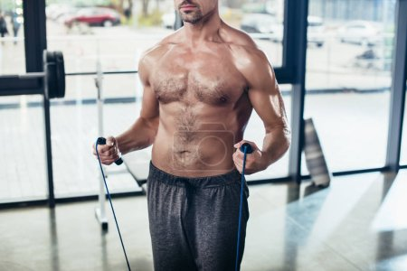 Photo for Cropped image of shirtless sportsman training with jumping rope in gym - Royalty Free Image