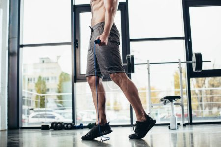 Photo for Low section of shirtless sportsman training with jumping rope in gym - Royalty Free Image