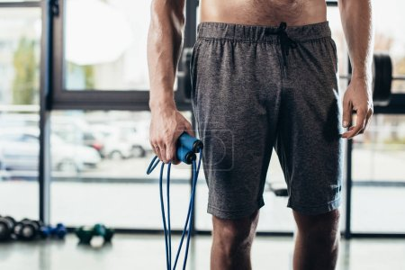 Photo for Mid section of shirtless sportsman holding jumping rope in gym - Royalty Free Image