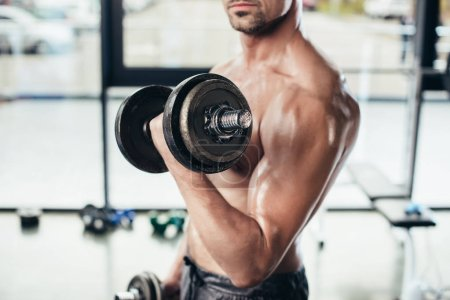 Photo for Cropped image of shirtless sweaty sportsman training with dumbbells in gym - Royalty Free Image