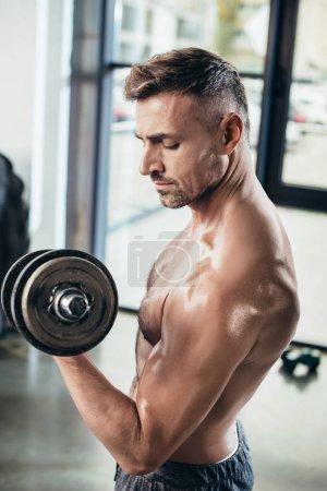 Photo pour Vue de côté de beau sportif torse nu, formation avec haltère dans une salle de sport - image libre de droit