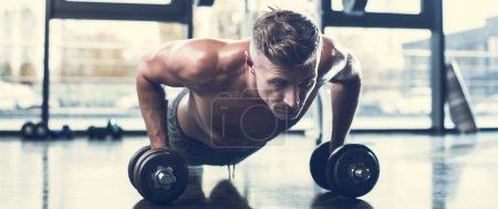 Photo for Handsome shirtless sportsman training with dumbbells and doing plank in gym - Royalty Free Image