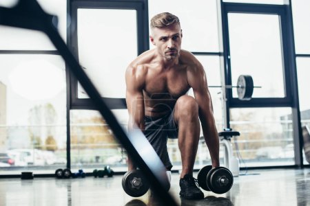 Photo for Selective focus of handsome shirtless sportsman training with dumbbells in gym - Royalty Free Image