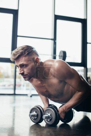 Photo pour Portrait de beau sportif torse nu, faisant la planche sur les haltères dans la salle de gym - image libre de droit