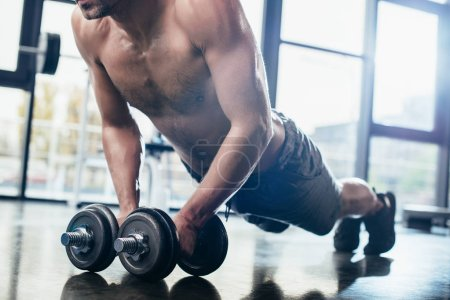 Photo for Cropped image of shirtless sportsman doing plank on dumbbells in gym - Royalty Free Image