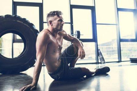 Photo pour Beau sportif torse nu assis sur le plancher dans la salle de gym et à la recherche. - image libre de droit
