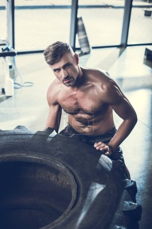 Photo for Handsome shirtless sportsman lifting tire in gym and looking at camera - Royalty Free Image