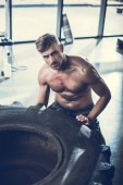 handsome shirtless sportsman lifting tire in gym and looking at camera