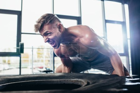 handsome shirtless sportsman lifting tire and screaming in gym