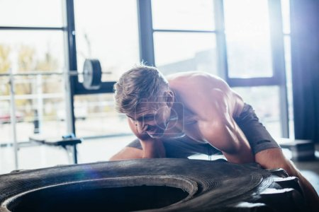 handsome shirtless sportsman lifting heavy tire in gym