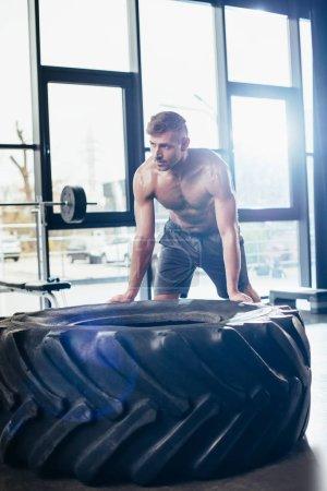 Photo pour Beau sportif torse nu, élaboration et pneu de levage dans la salle de gym - image libre de droit