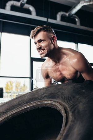 Photo for Handsome shirtless sportsman lifting tire and grimacing in gym - Royalty Free Image