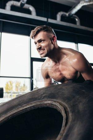 Photo pour Beau sportif torse nu levage pneu et grimaçant dans la salle de gym - image libre de droit