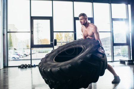 handsome muscular sportsman lifting tire in gym