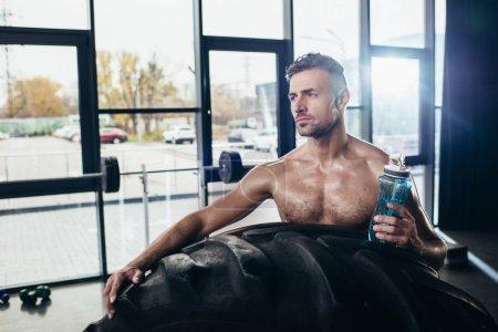 Photo pour Beau sportif torse nu penché sur pneu et tenant la bouteille de sport en salle de gym - image libre de droit