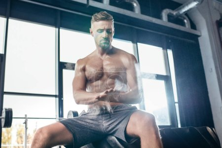 Photo for Handsome shirtless sportsman sitting on tire and applying talcum powder on hands in gym - Royalty Free Image