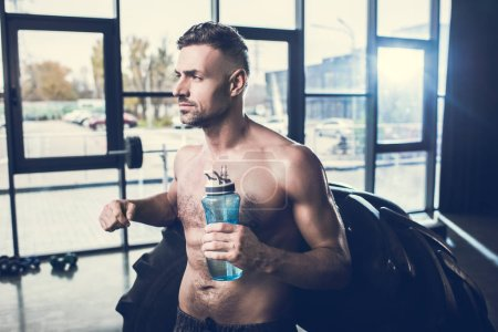 Photo for Handsome muscular sportsman leaning on tire and holding sport bottle in gym - Royalty Free Image