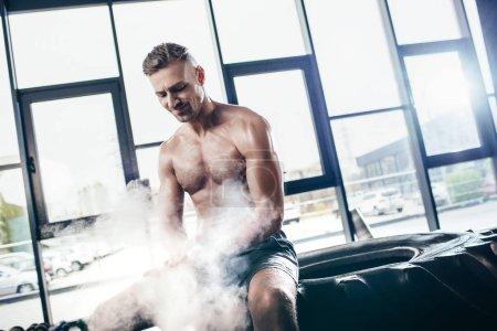 Photo pour Beau joyeux sportif torse nu assis sur le pneu et l'application de poudre de talc sur les mains dans la salle de gym - image libre de droit