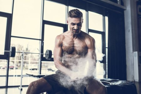Photo pour Beau sportif grimaçant assis sur le pneu et l'application de poudre de talc sur les mains dans la salle de gym - image libre de droit