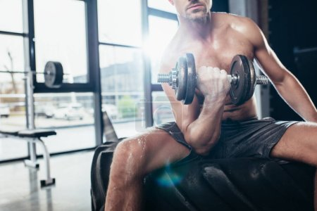 Photo for Cropped image of shirtless sportsman sitting on tire and exercising with in gym dumbbell - Royalty Free Image
