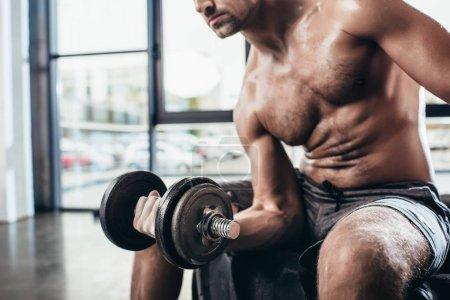 Photo pour Image recadrée de sueur sportif torse nu assis sur pneu et exercer avec haltère gym - image libre de droit