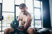 handsome shirtless sportsman sitting on tire and exercising with in gym dumbbell and looking down