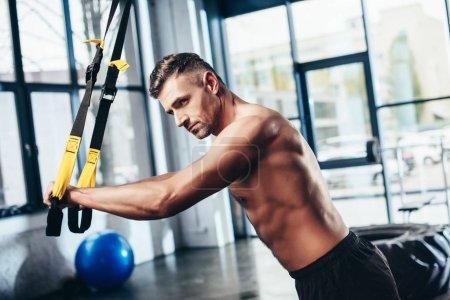 Photo pour Vue de côté de beau sportif torse nu de formation avec des bandes de résistance dans la salle de gym - image libre de droit
