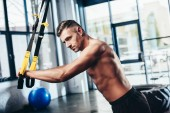 side view of handsome shirtless sportsman training with resistance bands in gym