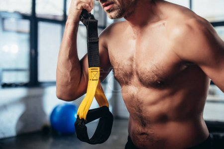 Photo for Cropped image of shirtless sportsman holding resistance bands in gym - Royalty Free Image