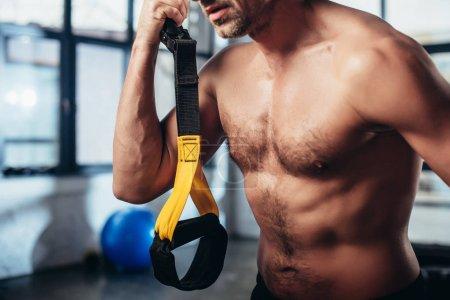 Photo pour Image recadrée de sportif torse nu tenant des bandes de résistance dans la salle de gym - image libre de droit