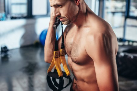 Photo pour Beau sportif torse nu musclé tenant des bandes de résistance dans la salle de gym - image libre de droit