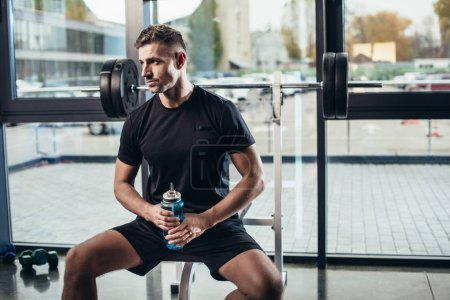 Photo for Handsome sportsman resting and holding sport bottle of water in gym - Royalty Free Image