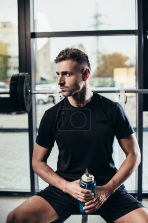 Photo pour Portrait de beau sportif au repos et tenant la bouteille de sport d'eau dans la salle de gym - image libre de droit