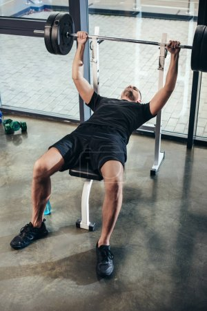 Photo for Handsome sportsman lifting barbell with weights while lying on bench in gym - Royalty Free Image