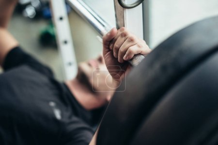 selective focus of sportsman lifting barbell with weights while lying on bench in gym