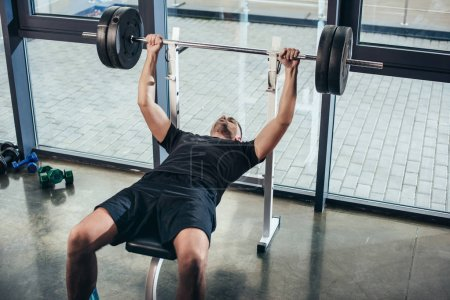 Photo for Handsome sportive man lifting barbell with weights while lying on bench in gym - Royalty Free Image
