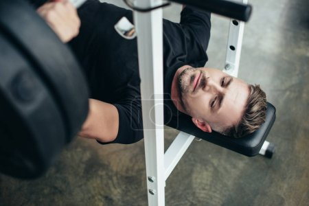 Photo for High angle view of handsome sportsman lifting barbell with weights while lying on bench in gym - Royalty Free Image