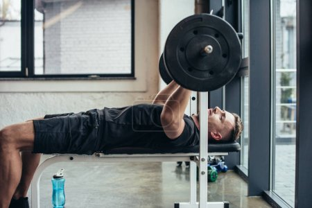 side view of handsome sportsman lifting barbell with weights while lying on bench in gym