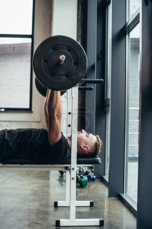 side view of handsome athletic man lifting barbell with weights while lying on bench in gym
