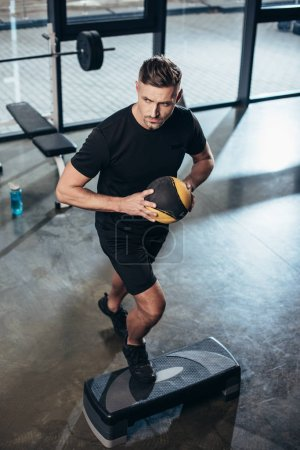 Photo for High angle view of handsome sportsman training on step platform with medicine ball in gym - Royalty Free Image