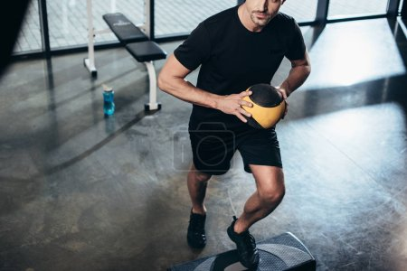 Photo for Cropped image of sportsman training on step platform with medicine ball in gym - Royalty Free Image