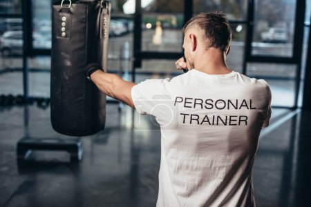 back view of personal trainer boxing with punching bag in gym