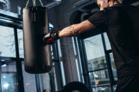 Photo pour Vue latérale du beau boxeur formation avec sac de boxe dans la salle de gym - image libre de droit