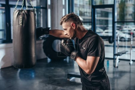 Photo pour Vue latérale du beau boxeur musculaire, entraînement avec sac de boxe dans la salle de gym - image libre de droit